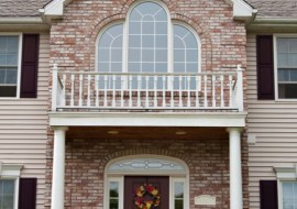 The front entrance of a large custom built luxury home in a residential neighborhood.